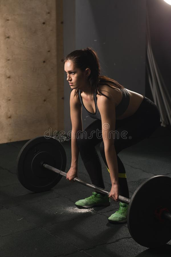 Femme musculaire dans le gymnase faisant des exercices lourds avec le barbell photo libre de droits