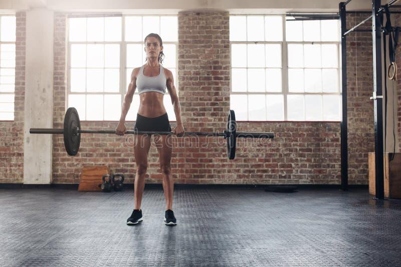 Femme musculaire dans un gymnase faisant des exercices lourds photographie stock libre de droits