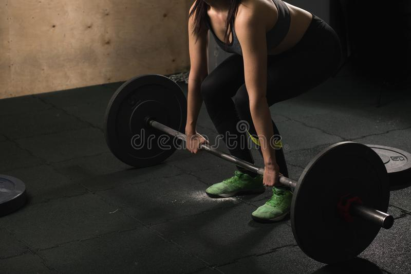 Femme musculaire dans un gymnase faisant des exercices lourds avec le barbell image stock