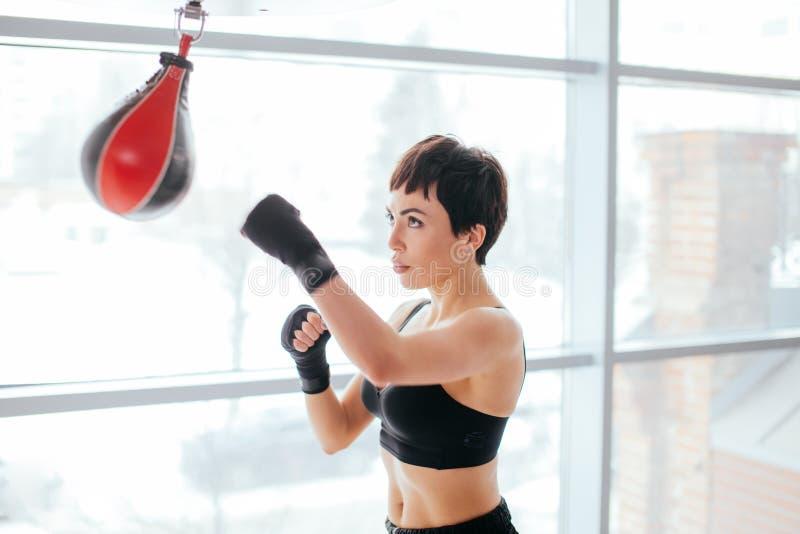 Femme musculaire en bandages et poires de boxe dans le studio images stock