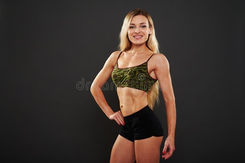 Femme musculaire sexy posant avec la main sur la hanche au-dessus du backgrou noir photographie stock libre de droits
