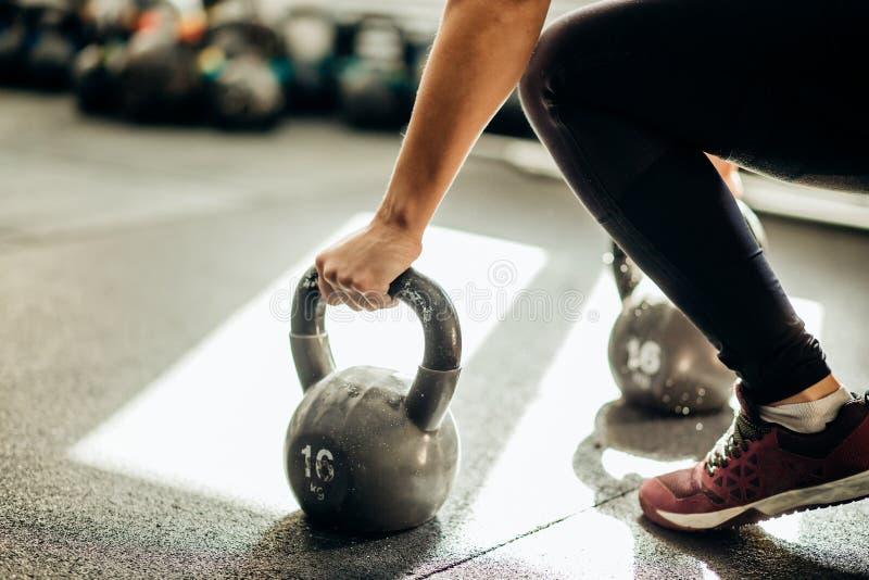 Femme musculaire tenant la vieille et rouillée cloche de bouilloire dessus sur le plancher de gymnase image libre de droits