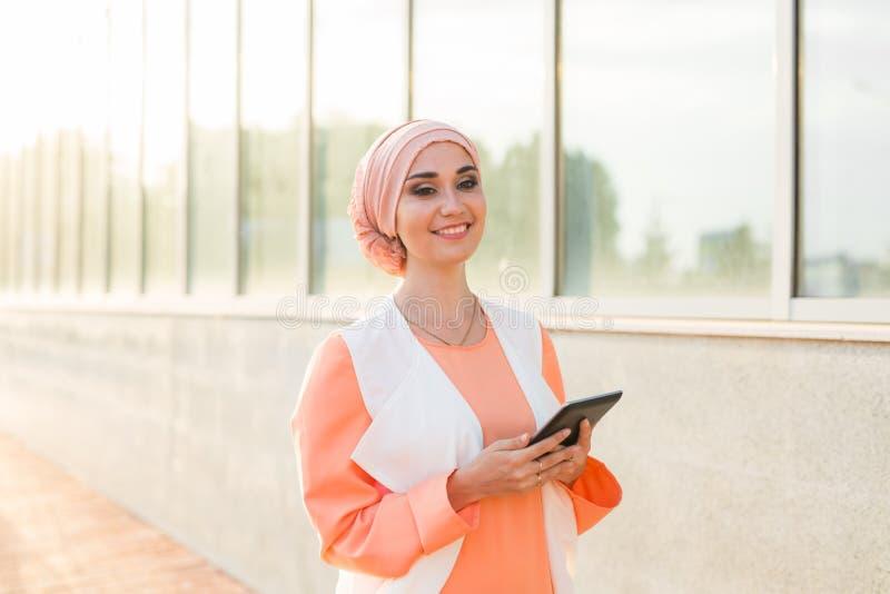 Femme musulmane Arabe moderne avec la tablette dehors image stock