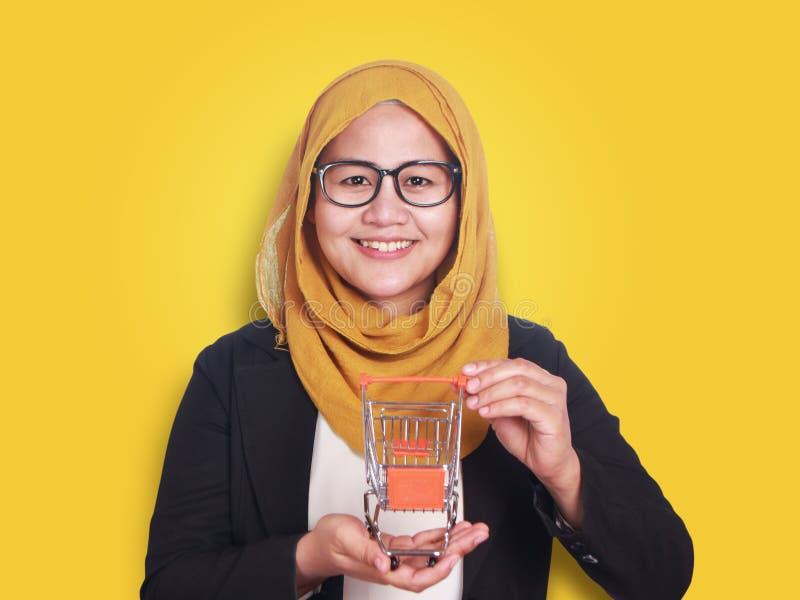 Femme musulmane asiatique réussie de sourire heureuse montrant le mini chariot de achat sur sa main, affaires en ligne de vente d photo stock
