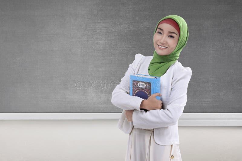 Femme musulmane assez asiatique tenant livre sacré Coran images libres de droits