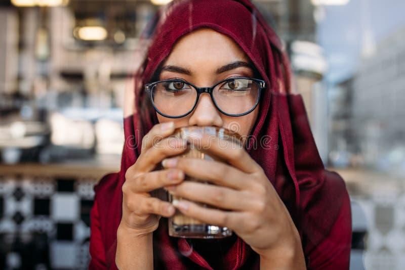 Femme musulmane ayant le café au café images stock