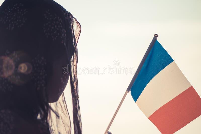 Femme musulmane dans l'écharpe avec le drapeau français de au coucher du soleil Concept photos libres de droits