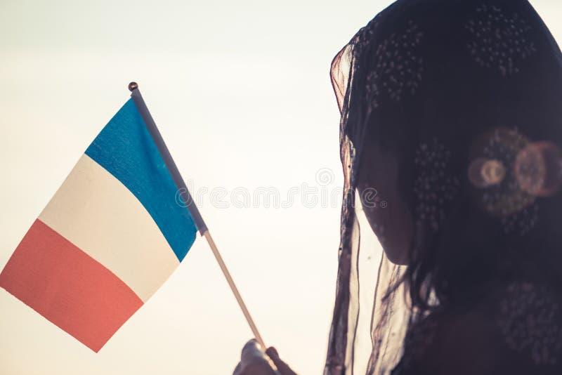 Femme musulmane dans l'écharpe avec le drapeau français de au coucher du soleil Concept photo libre de droits