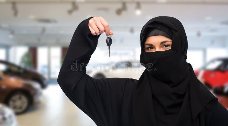 Femme musulmane dans le hijab avec la clé de voiture au-dessus du salon automobile photos stock