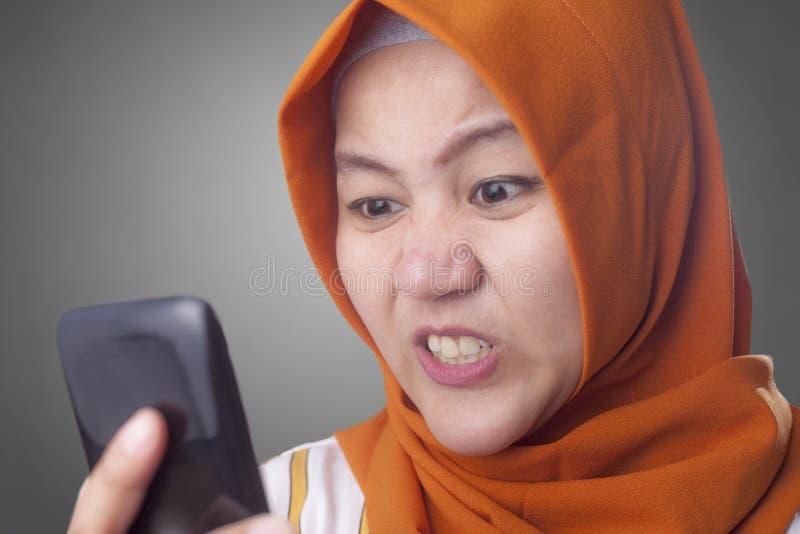 Femme musulmane f?ch?e tout en lisant le message textuel au t?l?phone intelligent photos libres de droits