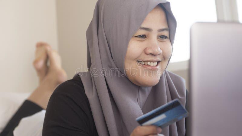 Femme musulmane faisant l'achat en ligne photographie stock libre de droits