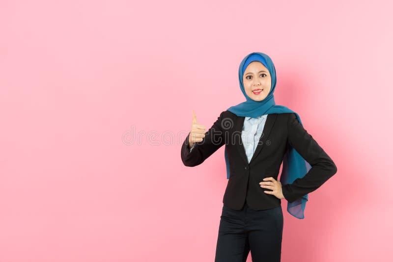 Femme musulmane heureuse de travailleur montrant le pouce vers le haut du geste photo stock