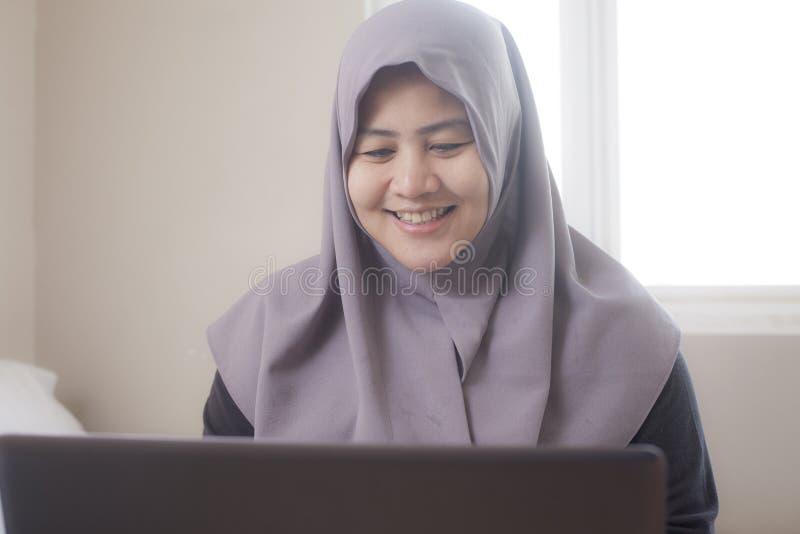 Femme musulmane heureuse travaillant avec l'ordinateur portable dans sa chambre ? coucher photographie stock libre de droits