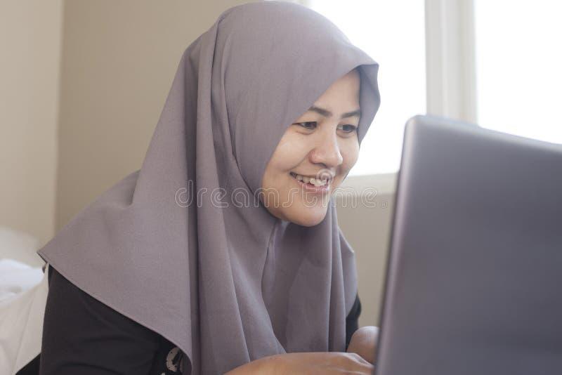 Femme musulmane heureuse travaillant avec l'ordinateur portable dans sa chambre ? coucher photos libres de droits