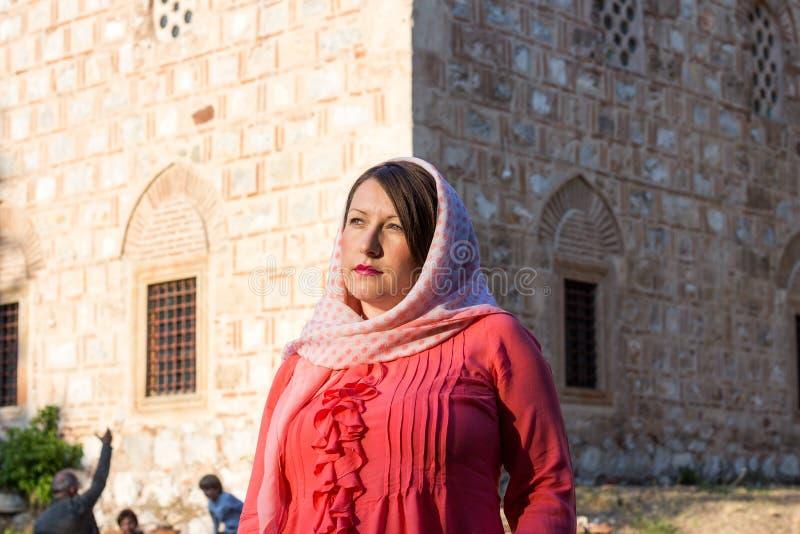 Femme musulmane identique moderne avec l'écharpe et les lunettes de soleil posant devant la mosquée images stock