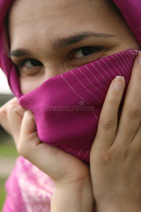 Femme musulmane souriant et cachant son visage photos libres de droits