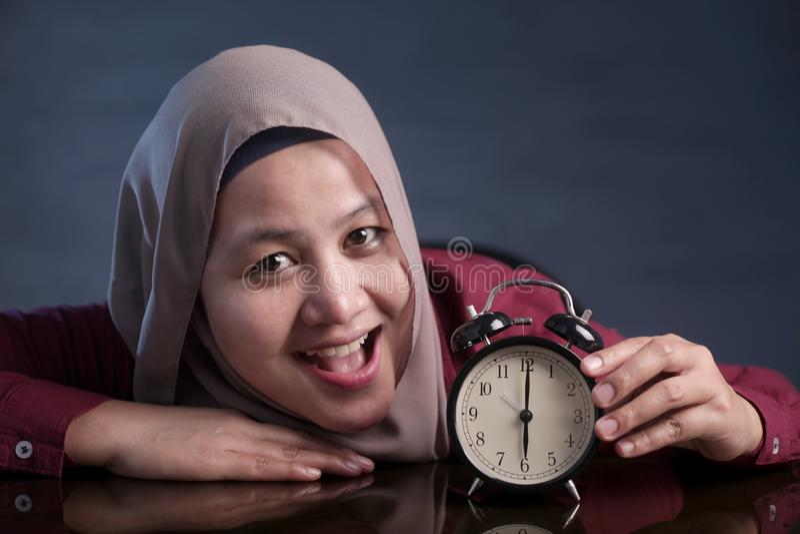 Femme musulmane tenant une horloge images stock