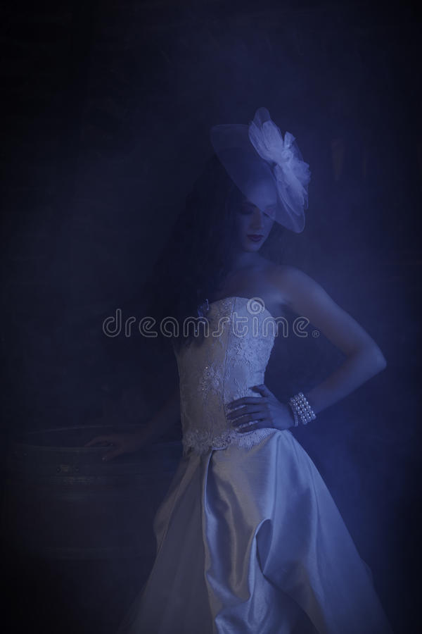 Femme mystérieuse dans la robe de mariage entourée par la brume fumeuse bleue photographie stock