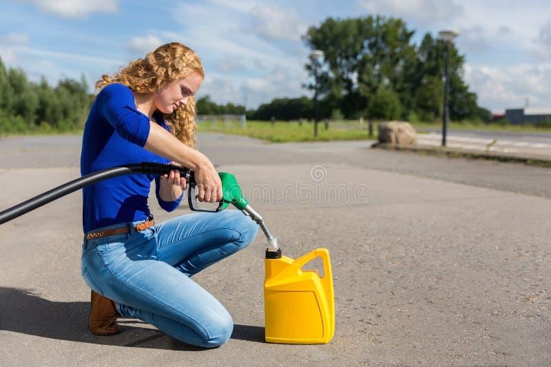 Femme néerlandaise remplissant de combustible le jerrycan avec le tuyau d'essence image libre de droits