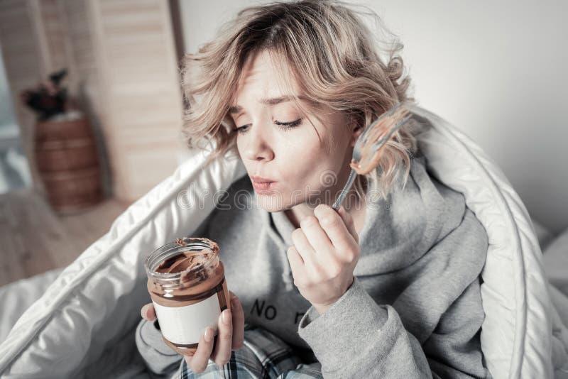 Femme n'allant pas n'importe où et ne mangeant pas du chocolat avec la cuillère photos stock