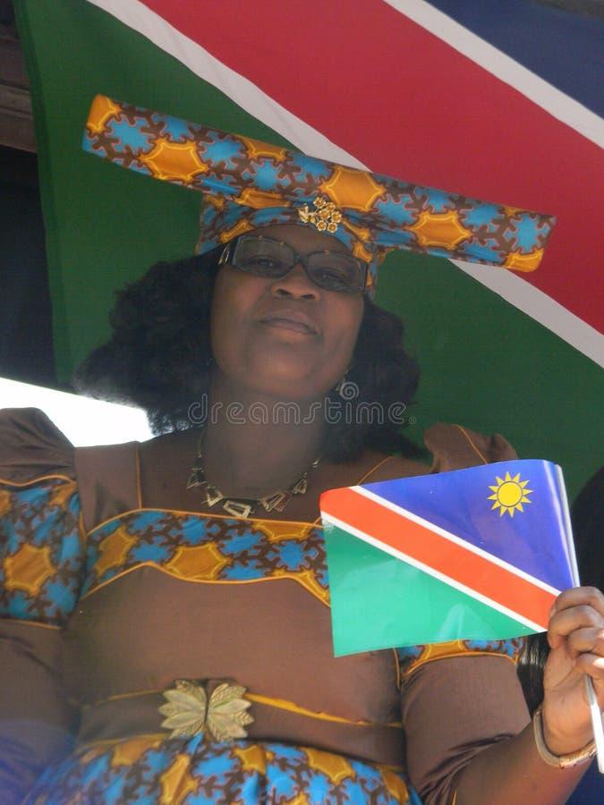 Femme namibienne dans la robe traditionnelle tenant le drapeau namibien photographie stock libre de droits