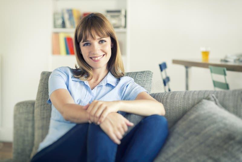 Femme naturelle de trente ans assise dans la maison moderne regard de l'appareil-photo photographie stock libre de droits