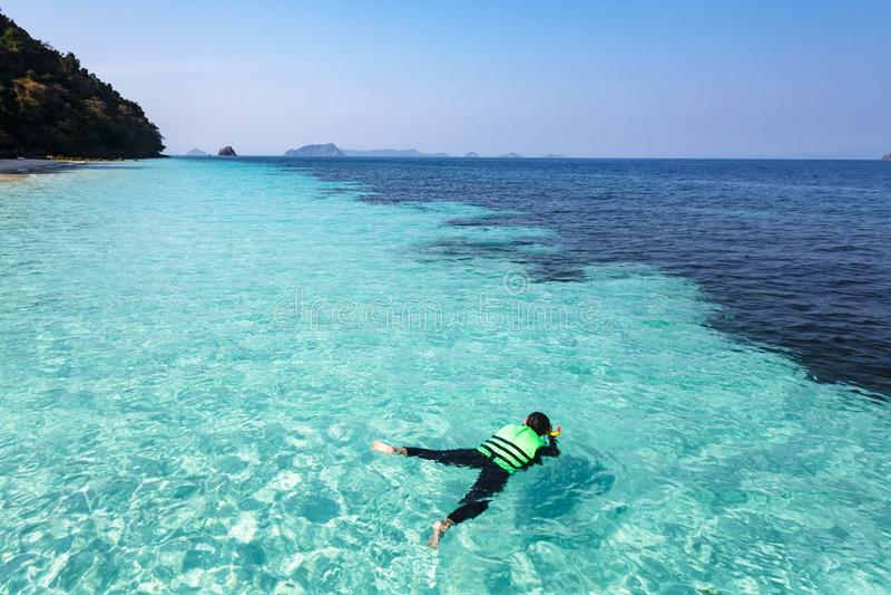 Femme naviguant au schnorchel dans l'eau clair comme de l'eau de roche, mer d'Andaman photographie stock libre de droits