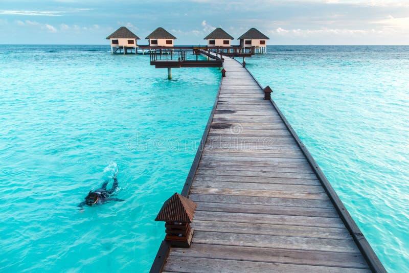 Femme naviguant au schnorchel au-dessus de l'eau clair comme de l'eau de roche à la villa de l'eau photographie stock