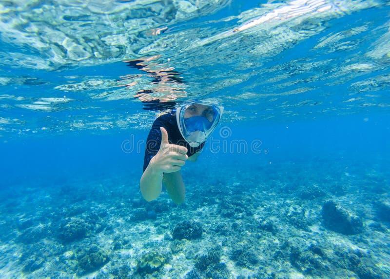 Femme naviguant au schnorchel en eau de mer peu profonde La prise d'air montre le pouce dans le plein masque protecteur photos stock