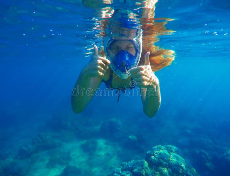 Femme naviguante au schnorchel montrant sous l'eau des pouces Prise d'air dans le plein masque protecteur photo stock