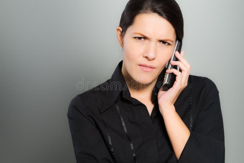 Femme nerveuse causant sur son mobile image stock