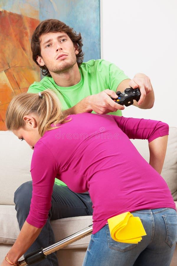 Femme nettoyant la maison et son mari avec la console photo libre de droits