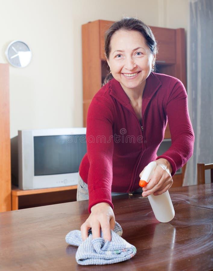 Femme nettoyant la table photographie stock