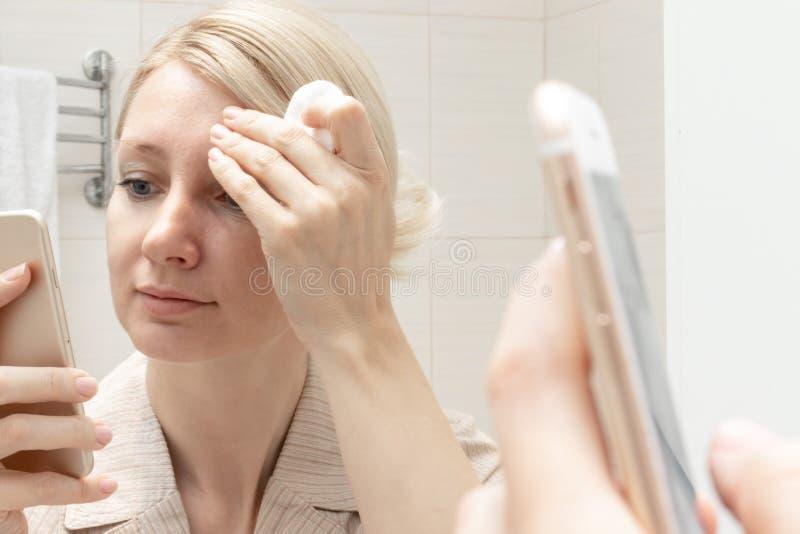 Femme nettoyant son visage avec une protection de coton et observant un smartphone dans sa main Concept de dépendance d'Internet image libre de droits