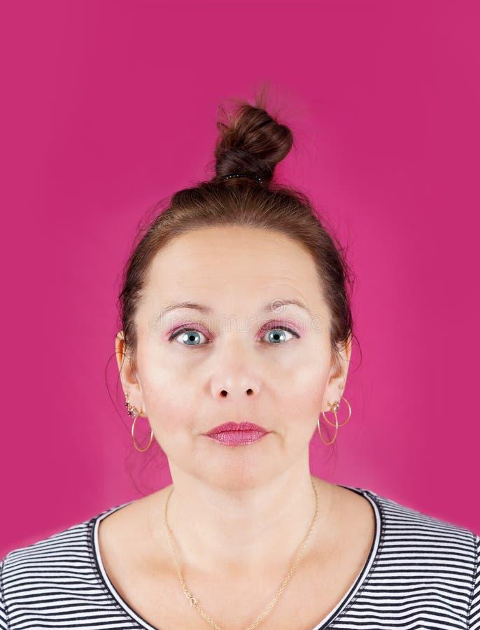 Femme neutre de visage sur le rose image stock
