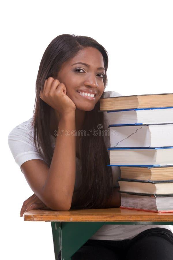 Femme noire d'étudiant universitaire par la pile de livres image libre de droits