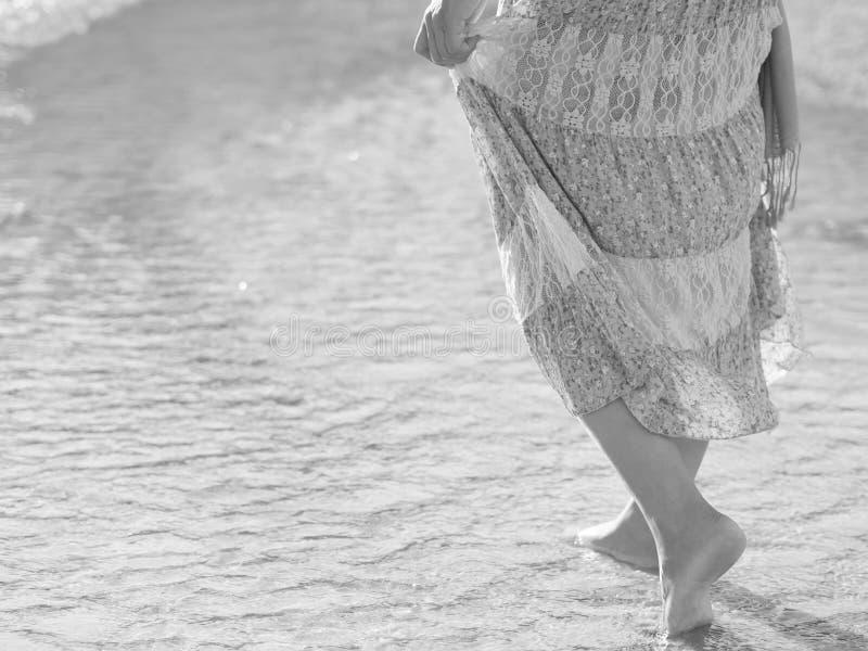 Femme noire et blanche marchant sur la plage de sable photos stock