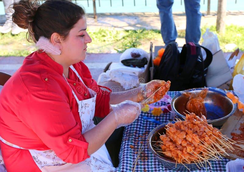 Femme non identifiée préparant des chiches-kebabs de poulet images libres de droits