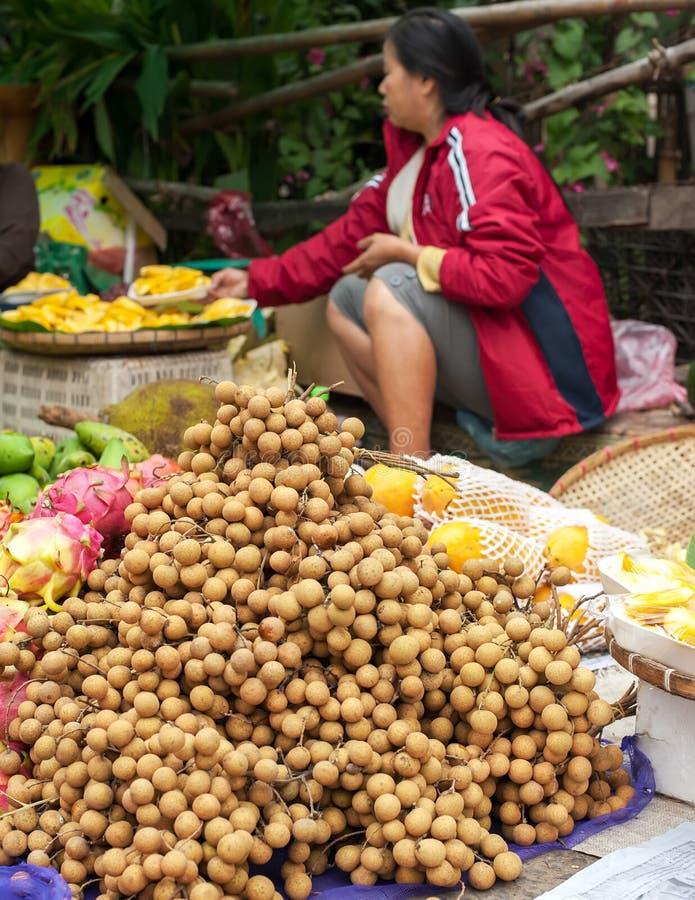 Femme non identifiée vendant des fruits au marché asiatique traditionnel laos images libres de droits