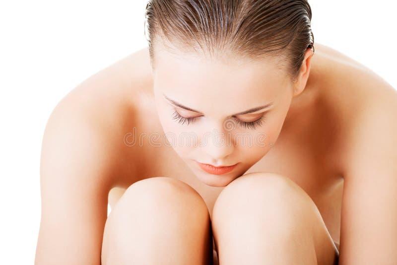Femme nue attirante s'asseyant se tenant. Plan rapproché. photographie stock libre de droits