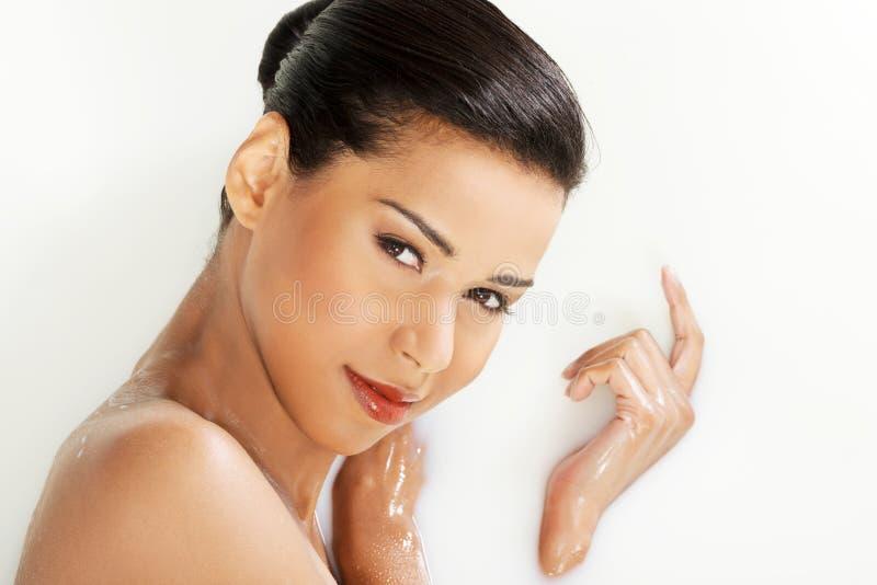 Femme nue attirante se situant dans un bain de lait. Avec le pétale de rose. Vers le haut de photo stock