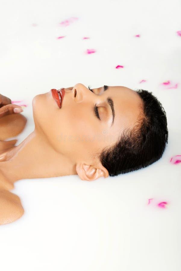Femme nue attirante se situant dans un bain de lait. Avec le pétale de rose. Vers le haut de image stock