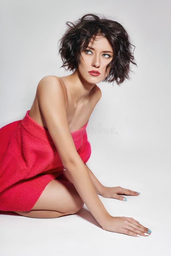 Femme nue avec les cheveux courts Fille posant dans un chandail rouge sur un fond blanc Peau propre parfaite, corps nu de image stock