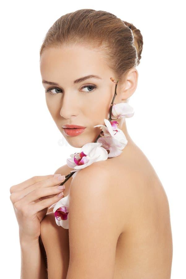 Femme nue nue ayant la fleur blanche sur des épaules. photographie stock