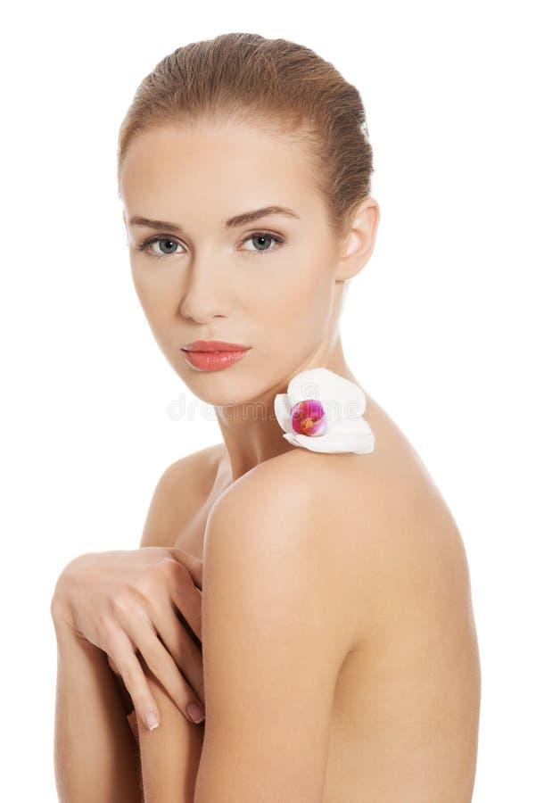 Femme nue nue ayant la fleur blanche sur des épaules. photo libre de droits