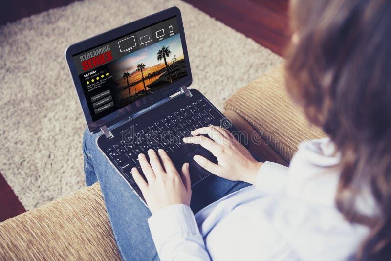 Femme observant coulant la série dans un ordinateur portable à la maison photographie stock