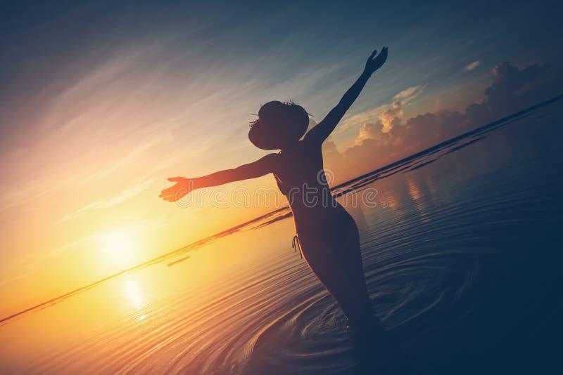 Femme observant le soleil se lever au-dessus de l'horizon à l'océan images libres de droits