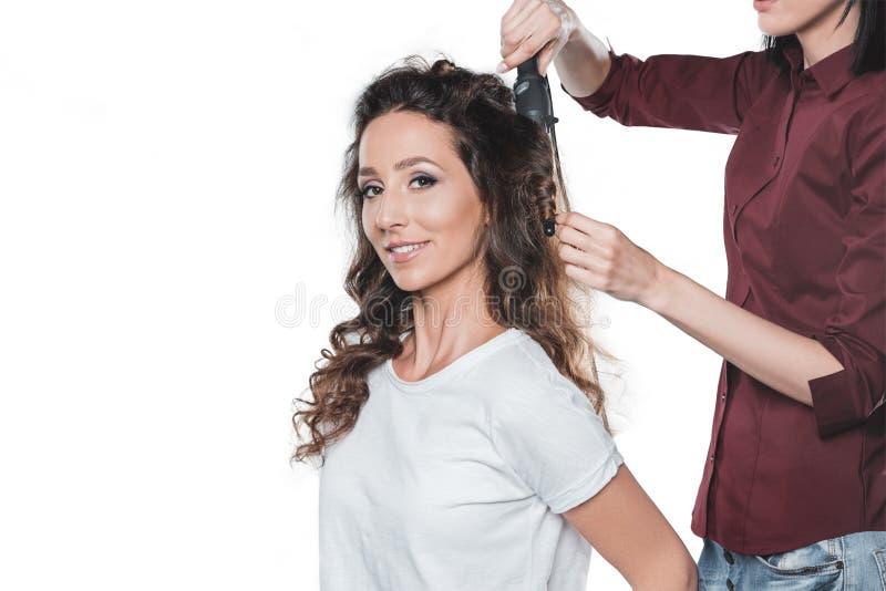 Femme obtenant des cheveux faits par la raboteuse de cheveux d'isolement sur le blanc photos libres de droits
