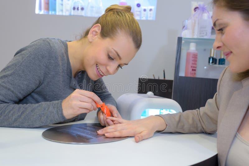 Femme obtenant des clous faits au salon de beauté image libre de droits