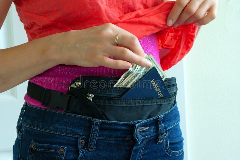 Femme obtenant l'argent liquide et le passeport de la ceinture d'argent cachée de voyage image libre de droits